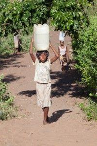 Muchos niños cargan con agua para uso doméstico.